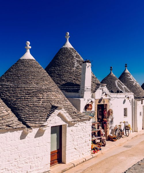 Houses of the tourist and famous Italian city of Alberobello, with its typical white walls and trulli conical roofs.